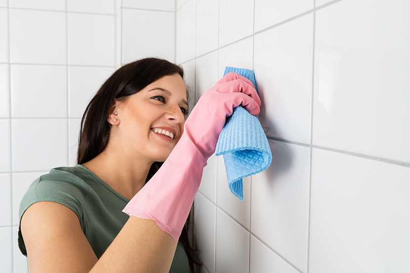 Žena čistící spáry kachliček