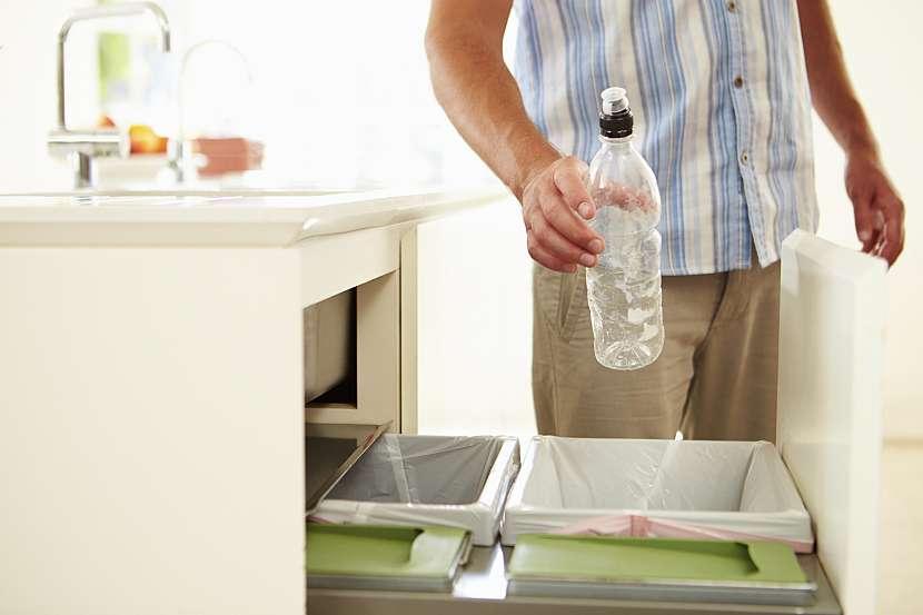 Muž vyhazuje plastovou lahev do koše
