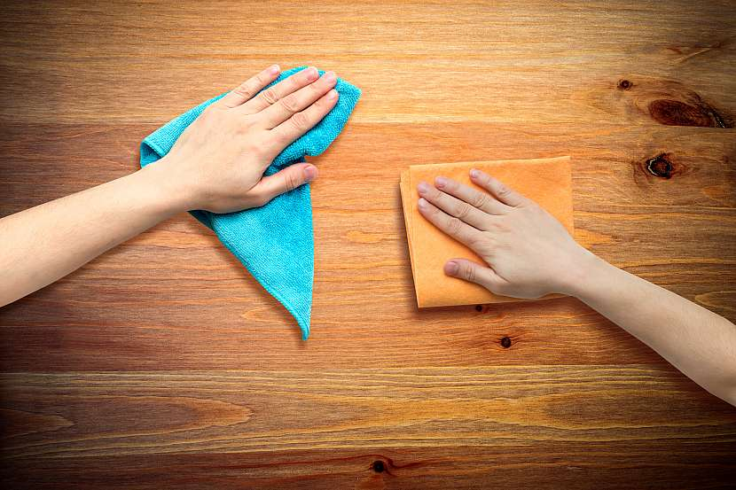 Dvě ruce čistící skvrny na dřevě