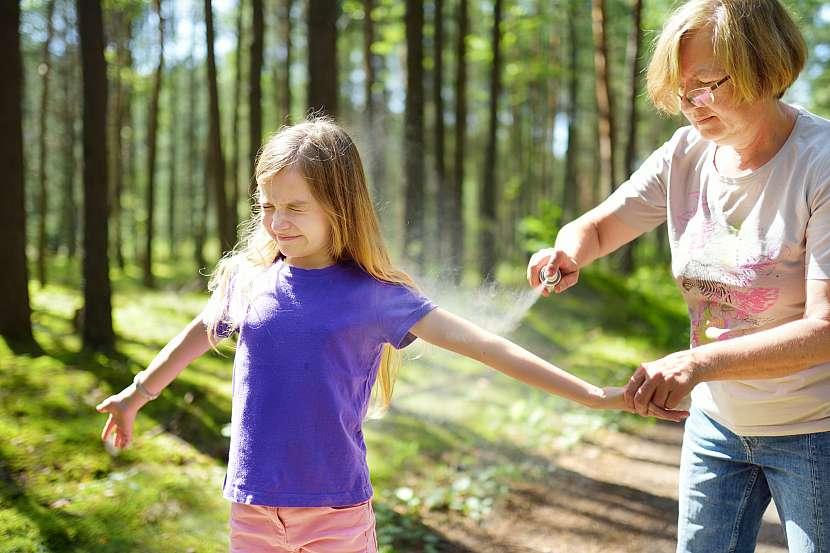 Maminka stříká dcerku uprostřed lesa repelentem