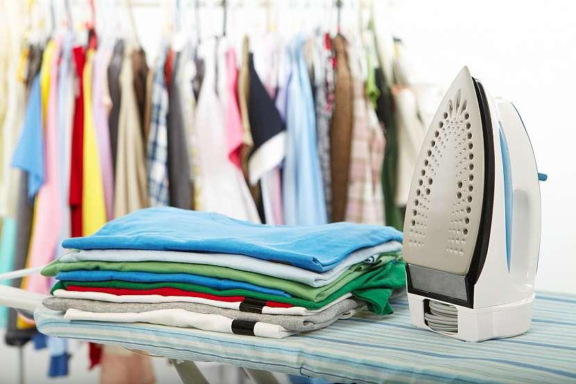 Žehlicí prkno s žehličkou a hromadou prádla