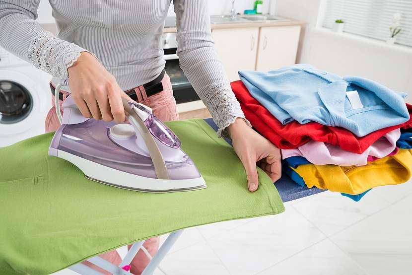 Žena žehlí na žehlícím prkně trička a vedle má komínek poskládaných triček