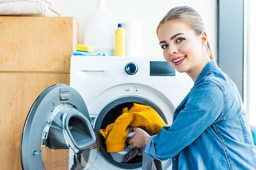 Žena u pračky s prádlem v ruce