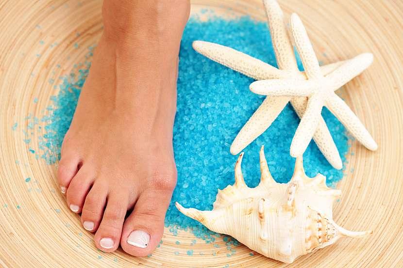 Noha v míse s modrou solí a mušlí a hvězdicemi