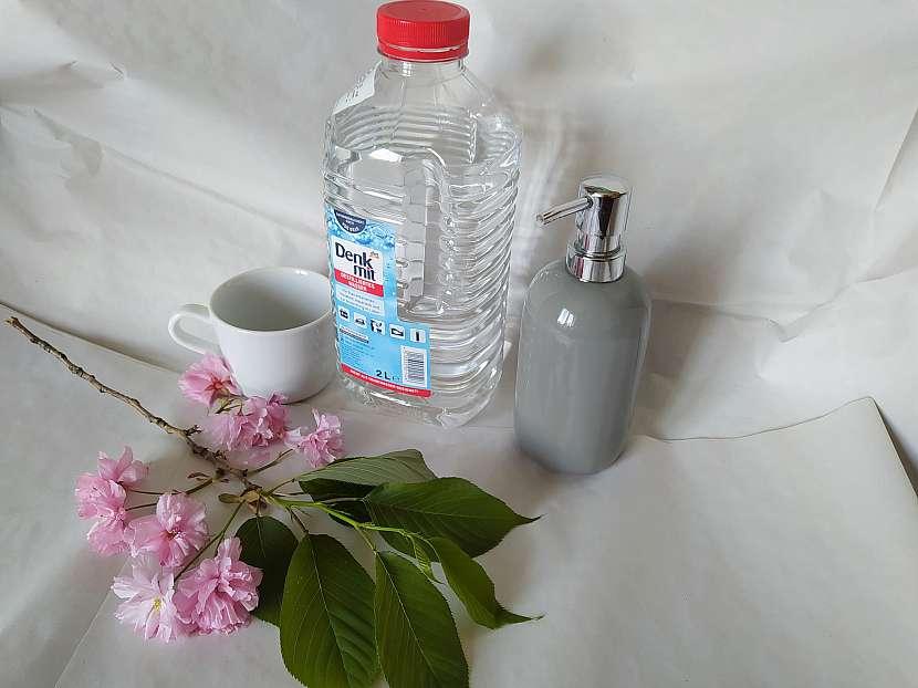 Destilovaná voda, šálek a dávkovač na mýdlo s třešňovou větví