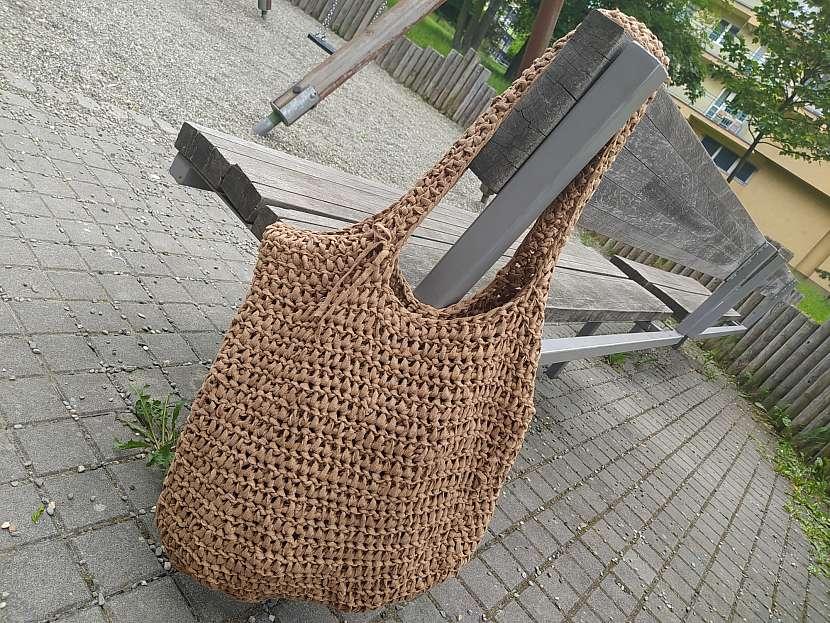 Háčkovaná taška zavěšená na lavičce