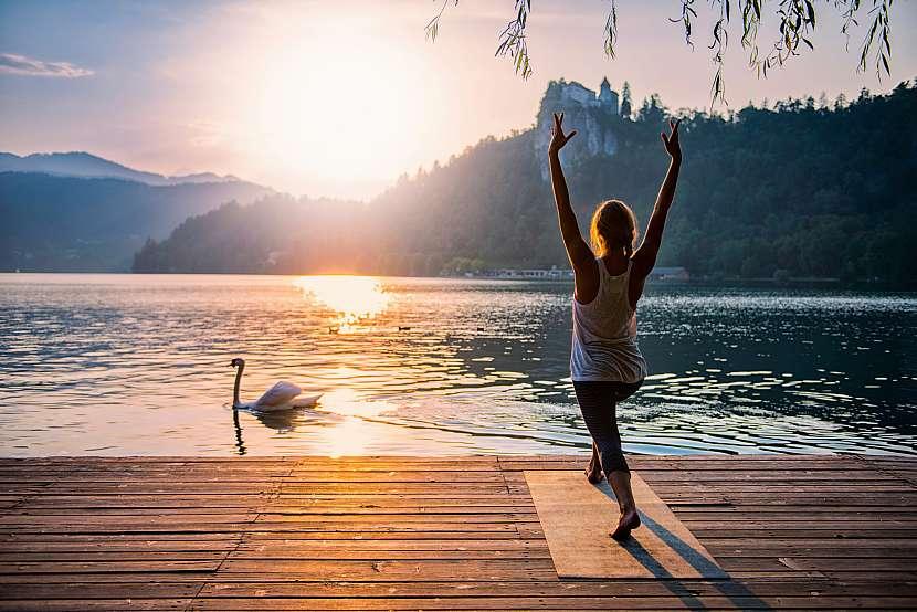 Žena cvičí jógu při východu slunce