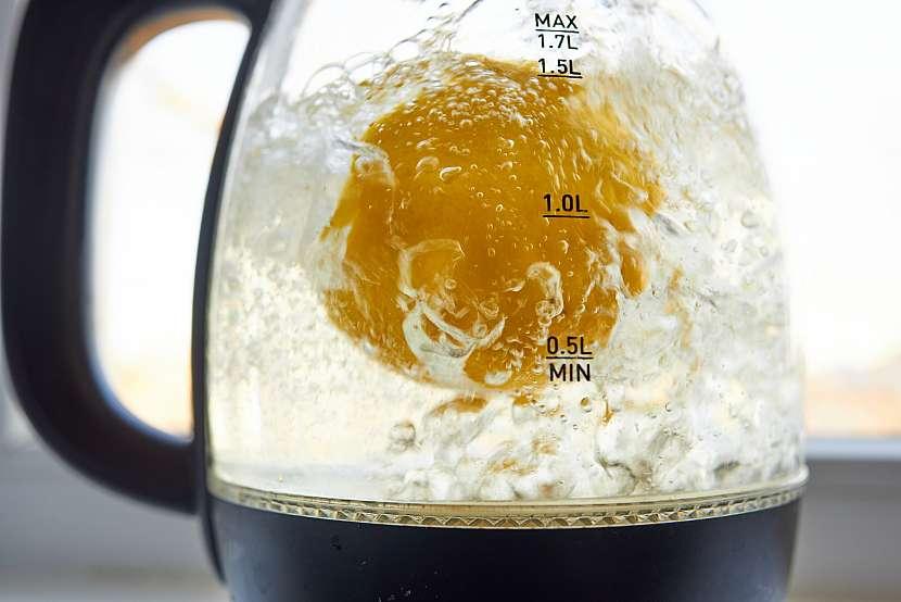 Konvice s citronovou vodou a kusem citronu.