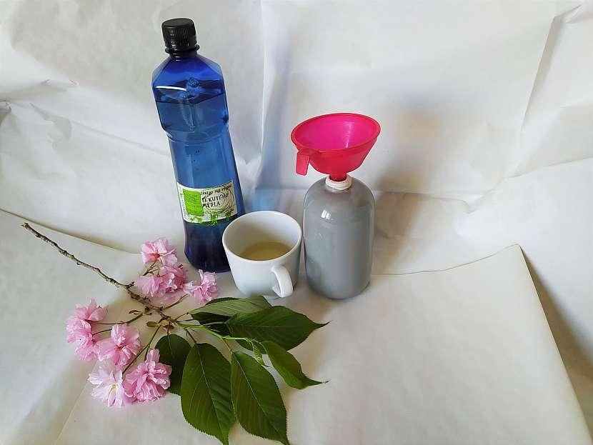 Nádoba na mýdlo s trychtýřem, hrnek s kastilským mýdlem, modrou lahví a třešňovou větví