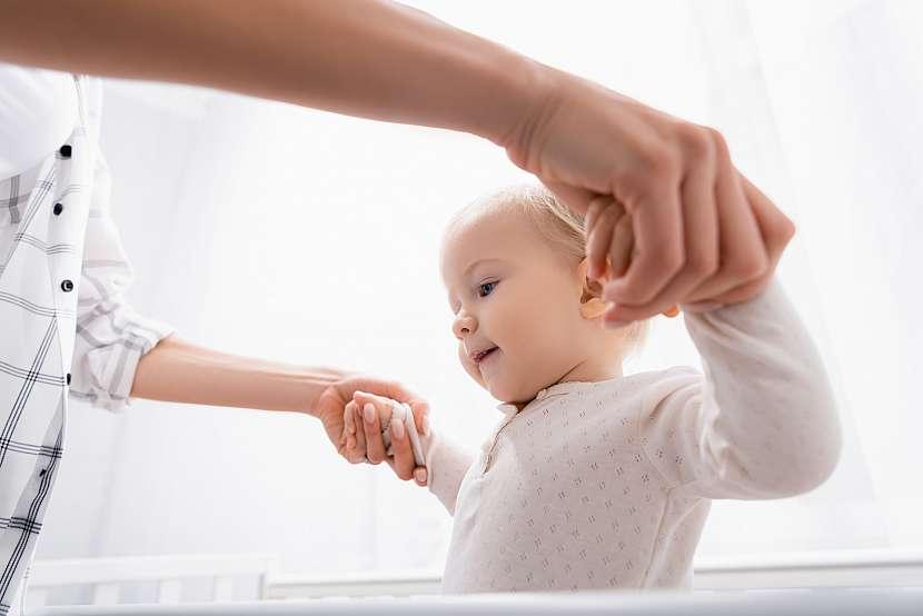 Dítě se drží matky za ruce