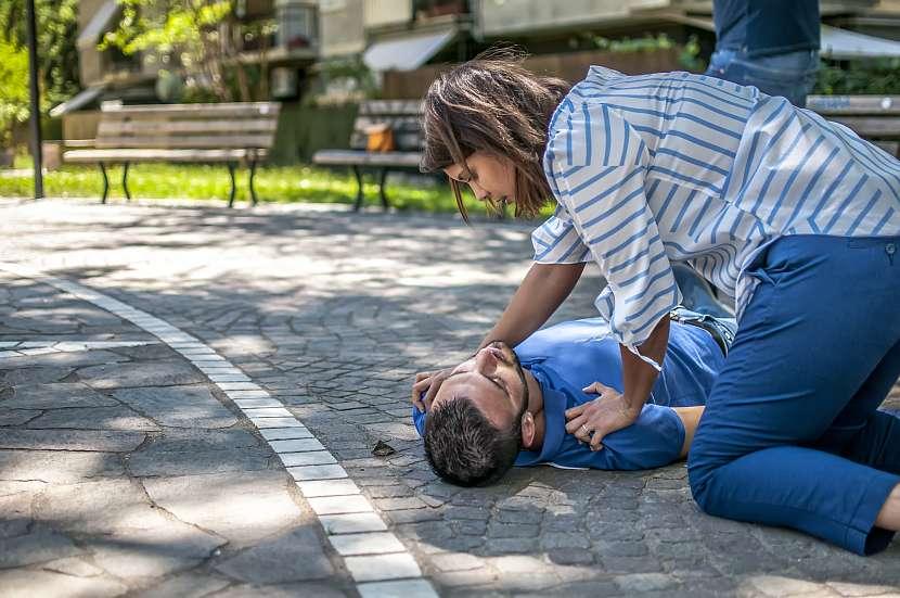 Žena poskytující první pomoc muži v bezvědomí