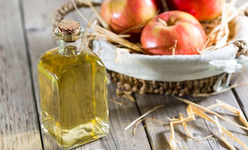 Lahvička bílého octu s miskou jablek