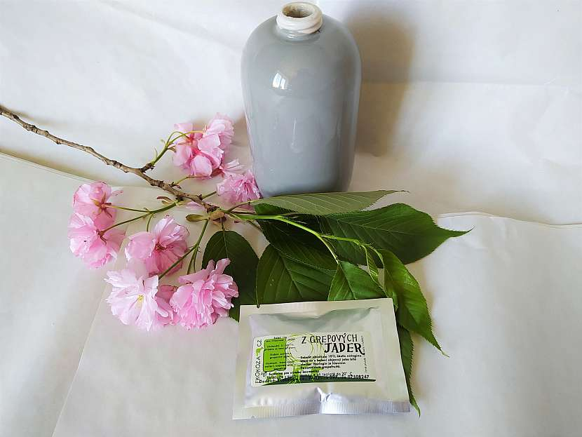 Grepový extrakt v balení, třešňová větvička a nádoba na mýdlo