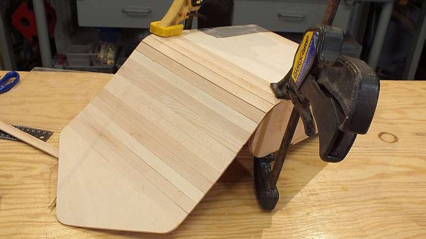 Jak se dělá dřevěný batoh: hotový díl přilepíme k přesahu plátna, stejně jako lišty roletky