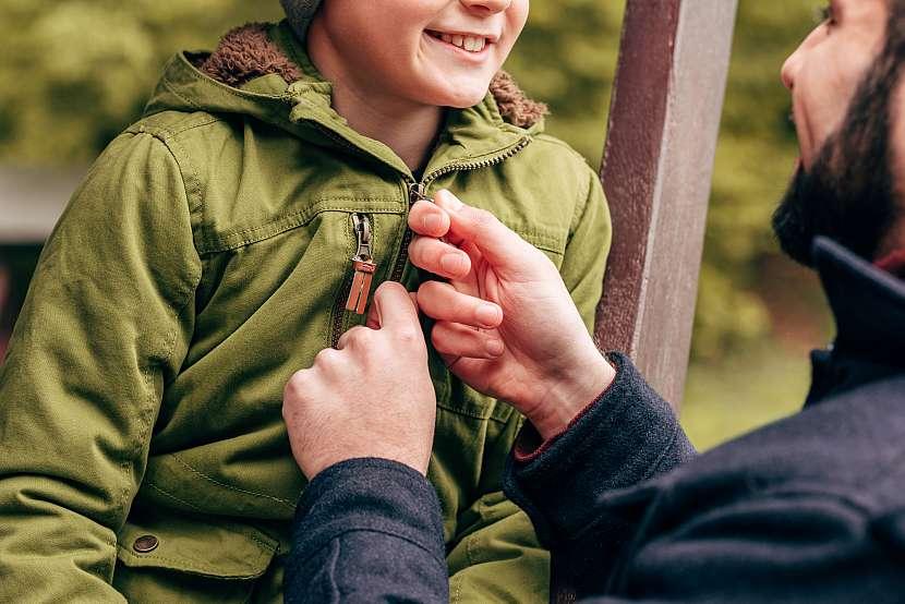Otec zapínající bundu svému synovi