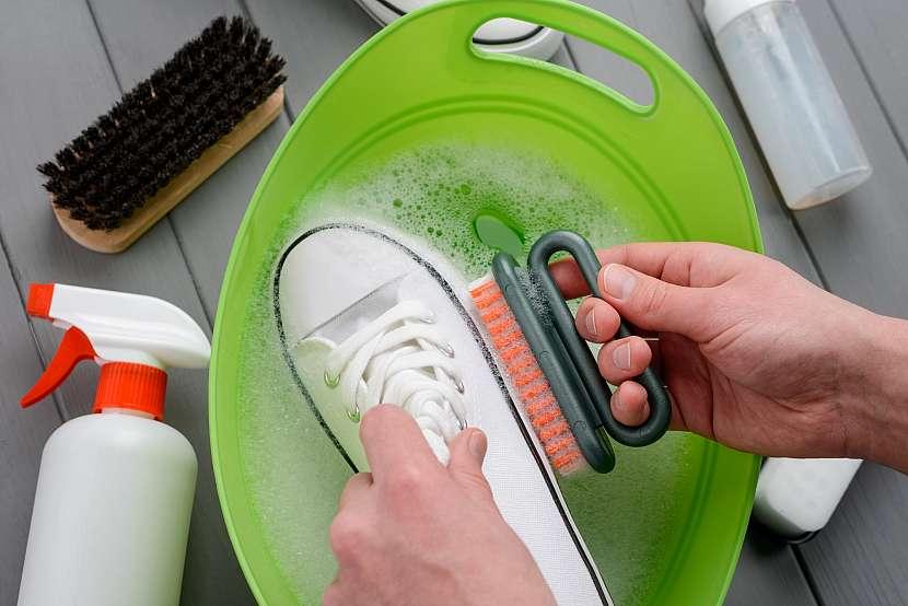 Drhnutí plátěných tenisek v kyblíku s mýdlovou vodou